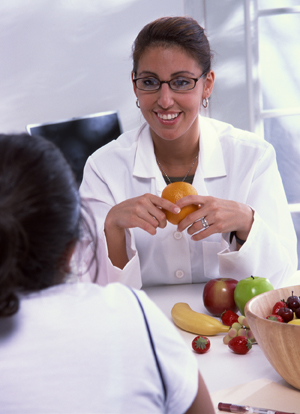 Healthcare provider talking to a patient about nutrition, with a variety of fresh fruit on the table